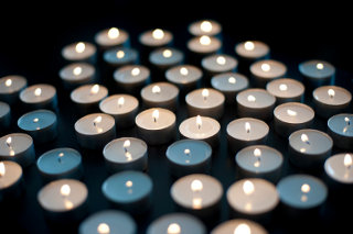 Array of small round burning candles against a dark background